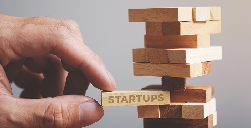 """A hand pulling out a piece of a wooden puzzle game that has """"Startups"""" written on it, risking the tower to fall over."""