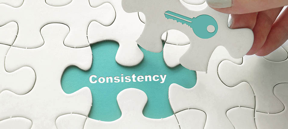 "A woman holding a puzzle piece with an image of a key on it to fit over a spot that says ""consistency."""